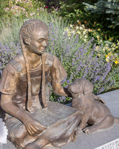Young Visions statue of girl with long braids, sitting crosslegged with on open book on her lap and petting her dog.