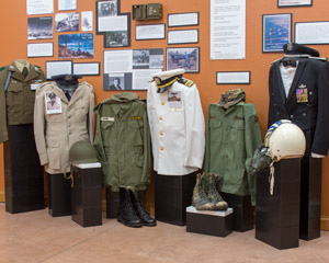 Display of Korean Conflict and Vietnam War era dress and field uniform shirts, helments, and boots in front of a wall of pictures and stories
